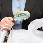 38811875 – close-up of businessperson checking bills with magnifying glass